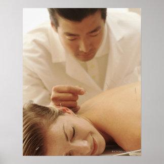 Acupuncturist que pone agujas en la mujer detrás póster