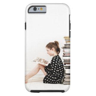 Adolescente que lee la historieta por la pila de funda resistente iPhone 6