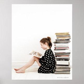 Adolescente que lee la historieta por la pila de poster