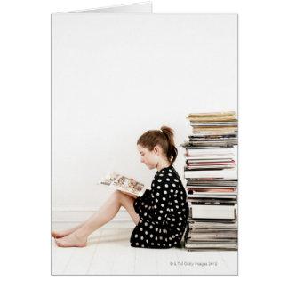 Adolescente que lee la historieta por la pila de tarjeta de felicitación