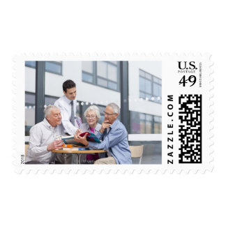 Adult students and teacher studying together in 2 postage