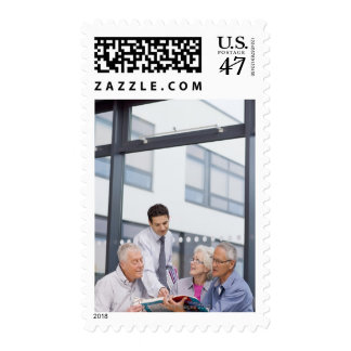 Adult students and teacher studying together in postage