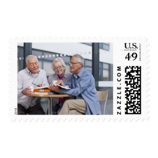 Adult students studying together in cafe postage stamp