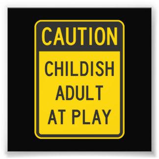 Adulto infantil de la precaución en el juego cojinete