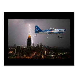 Aerobatic airplane in lightning postcard