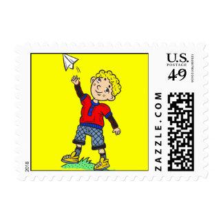 Aeroplano de papel que vuela del muchacho timbres postales