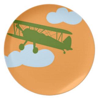 Aeroplano en fondo anaranjado llano platos