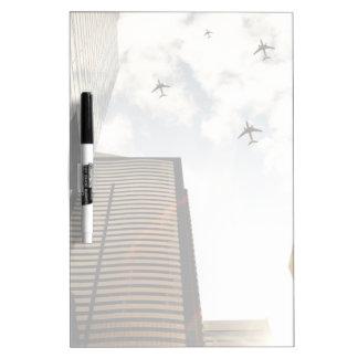 Aeroplanos que vuelan sobre edificios tableros blancos