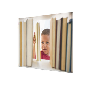 African American boy selecting book Canvas Print