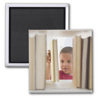 African American boy selecting book Magnet
