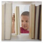 African American boy selecting book Tile