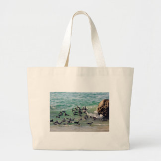 African penguins playing in the surf large tote bag