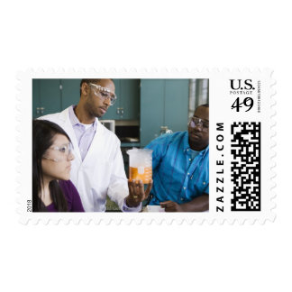 African teacher and students watching experiment stamp