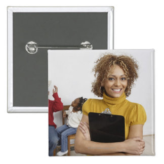 African teacher holding clipboard in front of 2 inch square button
