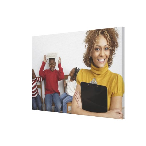 African teacher holding clipboard in front of canvas print