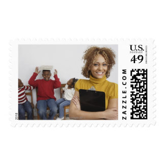 African teacher holding clipboard in front of postage stamp