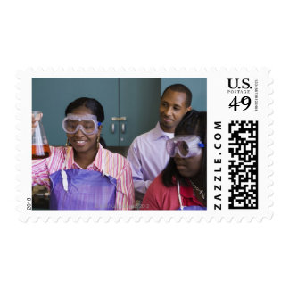 African teenage girl examining experiment in postage stamp
