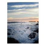Agite salpicar contra rocas en orilla en tarjetas postales