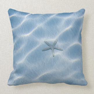 Agua azul ondulada con las estrellas de mar almohada
