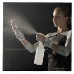 Agua de rociadura del gimnasta en las manos azulejos