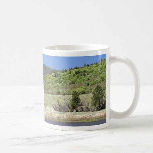 Agua del cielo de los árboles de las colinas de lo tazas de café