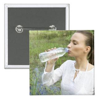 agua potable de la mujer joven de la botella pin