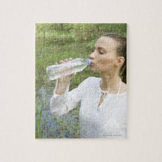 agua potable de la mujer joven de la botella puzzle