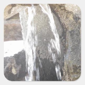 Agua que cae abajo sobre las rocas pegatina cuadrada