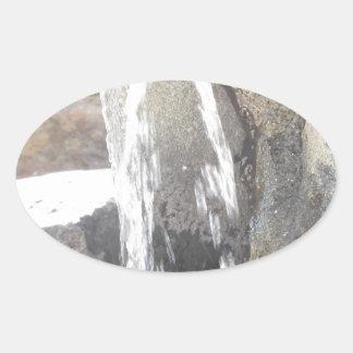 Agua que cae abajo sobre las rocas pegatina ovalada