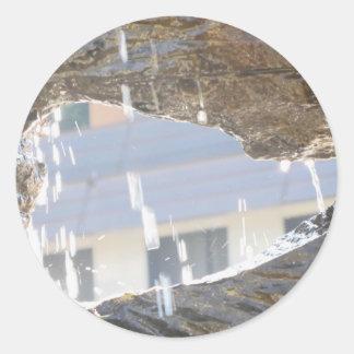 Agua que cae abajo sobre las rocas pegatina redonda