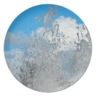 agua que salpica contra el cielo azul platos