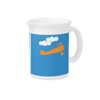 Airplane on plain blue background. beverage pitcher
