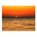 Ajuste anaranjado de la puesta del sol en aguas an postal