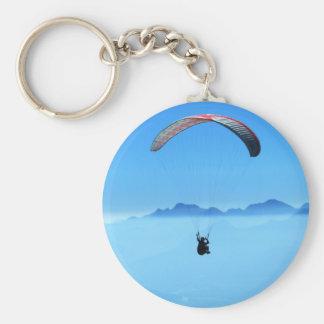 Ala flexible en fondo azul con las montañas llavero redondo tipo pin