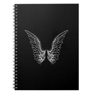 Alas blancas del ángel en fondo negro libros de apuntes con espiral