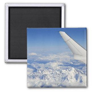 Alas del aeroplano del vuelo sobre las montañas fr imán cuadrado