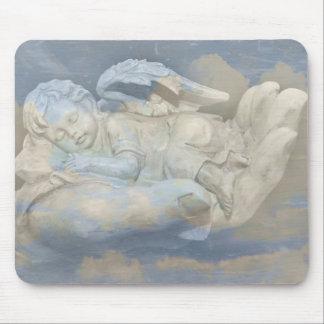 Alas del ángel del bebé que duermen en la mano de  tapete de raton