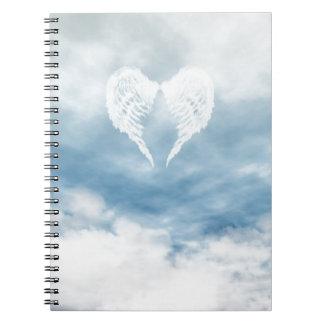 Alas del ángel en cielo azul nublado libros de apuntes