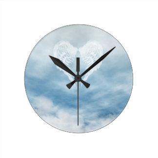 Alas del ángel en cielo azul nublado reloj redondo mediano