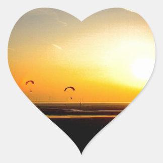 Alas flexibles que disfrutan de la puesta del sol pegatina en forma de corazón
