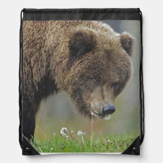 Alaskan Brown Bear eating dandelion Drawstring Bags