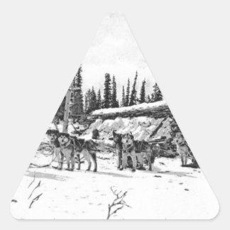 Alaskan Sled Dogs Standing Outside a Log Cabin Triangle Sticker