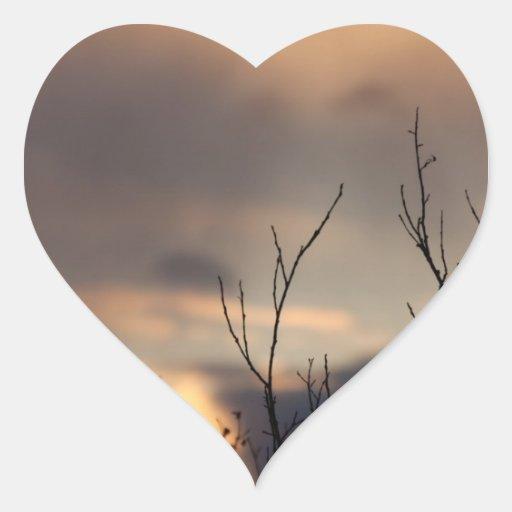 Alcance para la puesta del sol pegatina corazón