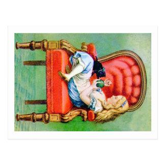 Alicia y su gato Dinah en la silla roja grande del Postal