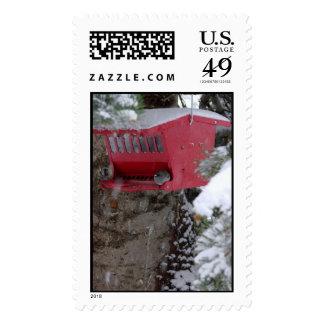 Alimentador rojo del pájaro en la nieve sello