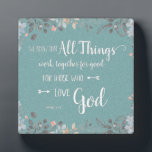 """All Things Work Together - Rom 8:28 Plaque<br><div class=""""desc"""">Plaque with distressed white typography on textured aqua background surrounded by watercolor flowers,  with well known verse from Romans 8:28,  """"… All things work together for good for those who love God…""""</div>"""