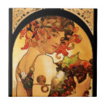 """Alphonse Mucha Fruit Tile<br><div class=""""desc"""">Alphonse Mucha Fruit tile. Lithograph poster from 1897. Czech artist Alphonse Mucha painted a variety of different allegories throughout his career. Fruit depicts a beautiful woman holding an armful of purple grapes, green pears, figs and red apples. The woman's dark hair is adorned with flowers and leaves, and she wears...</div>"""