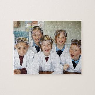 Alumnos (9-12) en la clase de la ciencia, sonriend rompecabeza