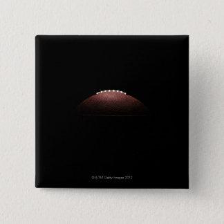 American football ball on black background pinback button