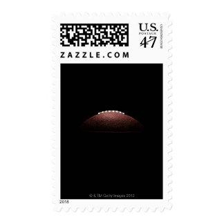 American football ball on black background postage
